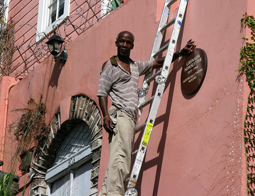 Workman placing plaque on Scott Street House